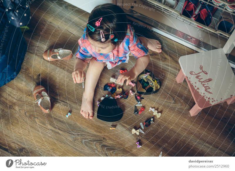 Baby Mädchen spielt mit Haarspangen, die auf dem Boden sitzen. Lifestyle Freude Glück schön Spielen Haus Kind Mensch Frau Erwachsene Kindheit Hand Mode