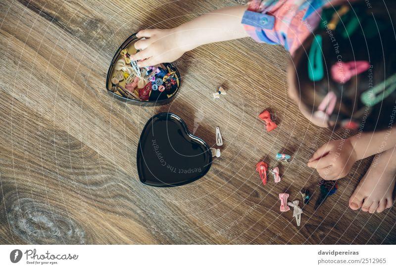 Baby Mädchen spielt mit Haarspangen, die auf dem Boden sitzen. Lifestyle Freude Glück schön Spielen Haus Kind Mensch Frau Erwachsene Kindheit Hand Bekleidung