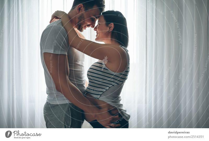 Mann umarmt seine schwangere Frau schön Mensch Baby Erwachsene Mutter Familie & Verwandtschaft Paar Vollbart Lächeln Liebe Umarmen authentisch Fröhlichkeit