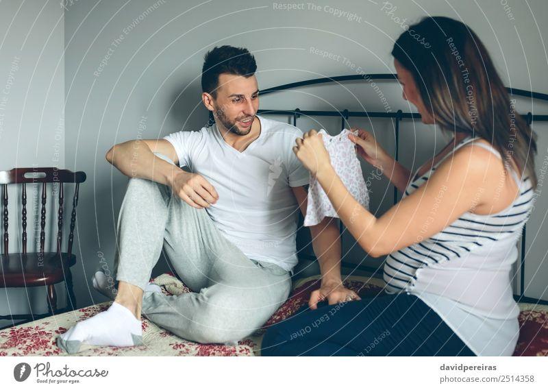 Schwangere zeigt ihrem Mann das Kleid. Glück schön Stuhl Schlafzimmer Mensch Baby Frau Erwachsene Mutter Vater Familie & Verwandtschaft Paar Partner Bekleidung