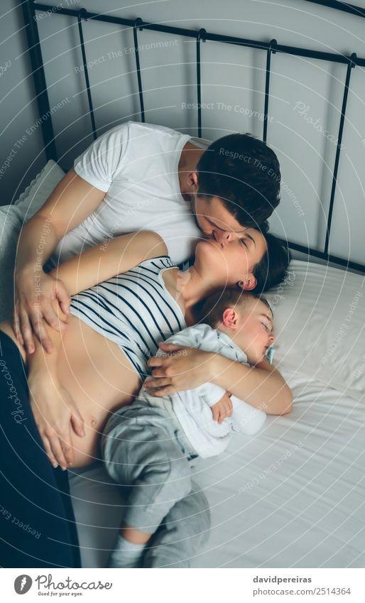 Schwanger, die ihre Partnerin mit ihrem Sohn küsst. Glück schön Leben Erholung Schlafzimmer Kind Mensch Baby Kleinkind Frau Erwachsene Mann Eltern Mutter Vater