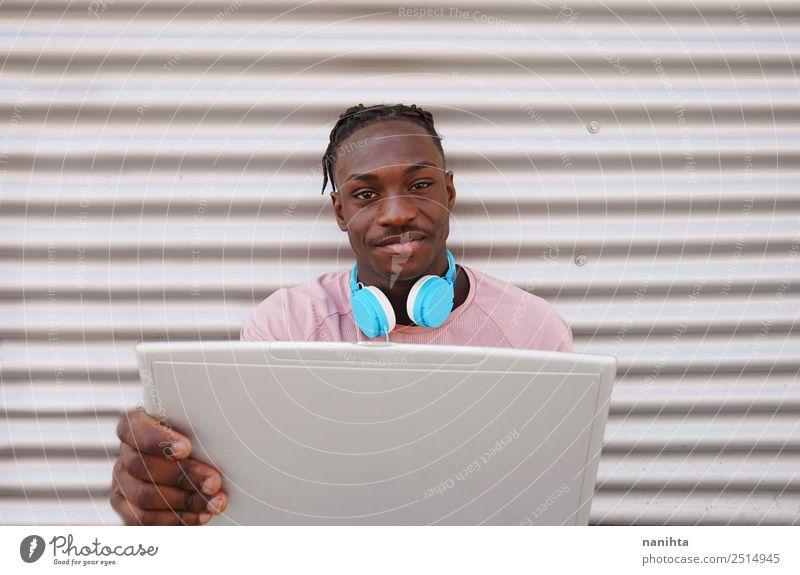 Junger schwarzer Mann mit seinem Laptop Lifestyle Stil Design Schüler Headset Computer Kopfhörer Notebook Technik & Technologie Unterhaltungselektronik Internet