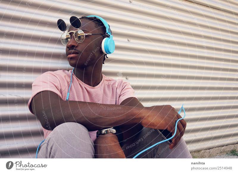 junger schwarzer Mann, der mit seinem Handy Musik hört. Lifestyle Stil Design Freizeit & Hobby Headset Kopfhörer Technik & Technologie Unterhaltungselektronik