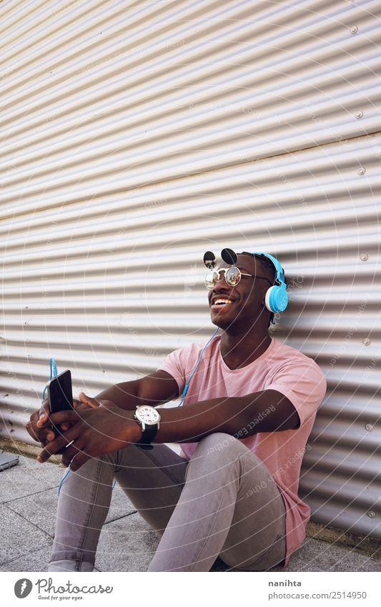 Junger glücklicher Mann, der Musik hört. Lifestyle elegant Stil Freude Freizeit & Hobby Handy Headset Kopfhörer Technik & Technologie Unterhaltungselektronik