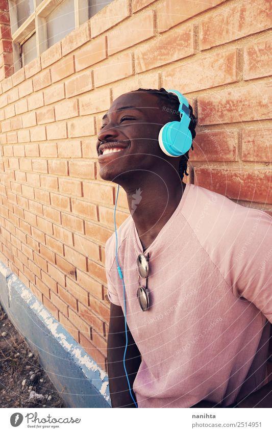 Junger glücklicher schwarzer Mann hört Musik. Lifestyle Stil Freude Wellness Wohlgefühl Zufriedenheit Headset Kopfhörer Technik & Technologie