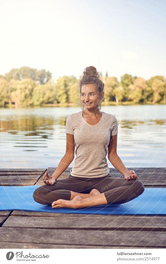 Lächelnde Frau, die auf einem Holzdeck meditiert. Lifestyle Glück Körper Wellness Meditation Sommer Meer Yoga Erwachsene 1 Mensch 18-30 Jahre Jugendliche Natur