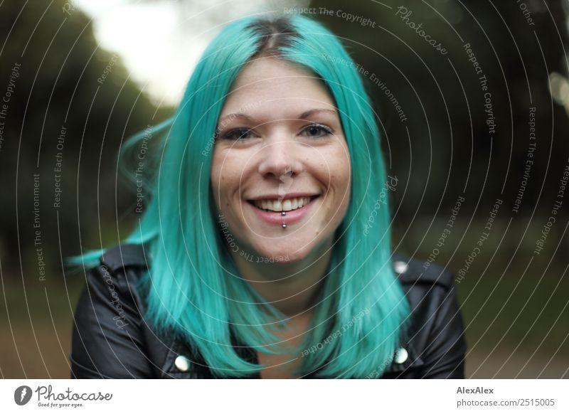 Portrait einer lächenden jungen Frau mit türkisen Haaren Stil schön Leben Junge Frau Jugendliche 18-30 Jahre Erwachsene Landschaft Park Lederjacke Schmuck