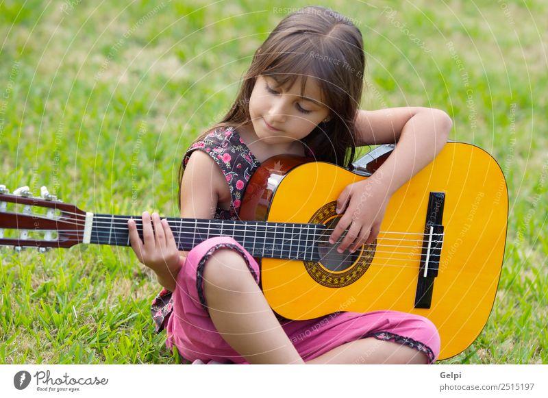Mädchen mit Gitarre Freude Glück schön Spielen Musik Kind Mensch Kindheit Hand Finger Musiknoten Gras sitzen Fröhlichkeit klein niedlich grün rosa unschuldig