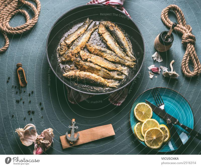 Gebratene Sardinen in der Pfanne auf dem Küchentisch mit Zutaten Lebensmittel Fisch Ernährung Abendessen Bioprodukte Vegetarische Ernährung Geschirr Teller