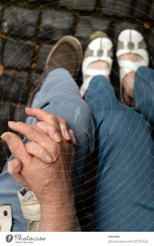 Seniorenpärchen hält Händchen Mensch Frau Erwachsene Mann Paar Partner Hand Finger Beine 2 Hose Jeanshose Schuhe Hand in Hand sitzen blau grau weiß Glück