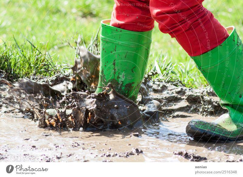 Mit grünen Gummistiefel in der Pfütze matschen Freude Kind Kindheit Beine 1 Mensch 3-8 Jahre 8-13 Jahre Jeanshose Stiefel springen dreckig braun rot stampfen