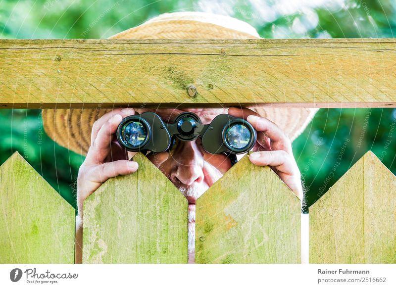 ein neugieriger Nachbar beobachtet mit einem Fernglas Mensch maskulin Mann Erwachsene Männlicher Senior 1 Natur Garten Park Hut Strohhut beobachten bedrohlich