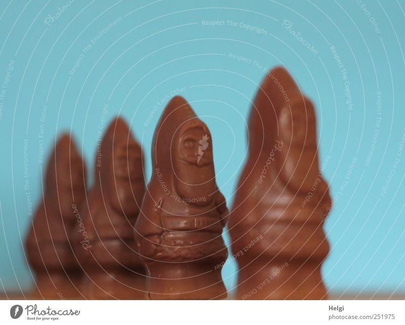 vier Schokoladenweihnachtsmänner stehen hintereinander vor türkisem Hintergrund Lebensmittel Süßwaren Weihnachtsmann Ernährung warten ästhetisch Zusammensein