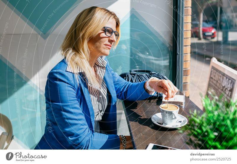 Junge Frau beim Mischen von Kaffee Lifestyle kaufen schön Freizeit & Hobby Tisch Arbeit & Erwerbstätigkeit Telefon PDA Mensch Erwachsene blond Denken