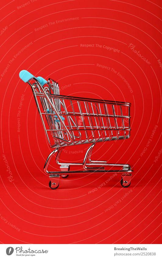 Leerer Einkaufswagen für den Spielzeugsupermarkt über rotem Hintergrund Metall klein kaufen Einkaufskorb Karre Handwagen Einzelhandel Konsum Profil Business
