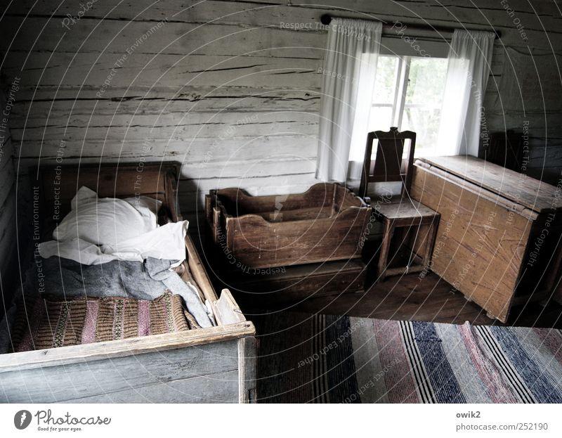 Ur-Ikea Häusliches Leben Wohnung Innenarchitektur Möbel Stuhl Bett Raum Wohnzimmer Kommode Teppich Holzwand Kissen Fenster Vorhang alt dunkel einfach historisch