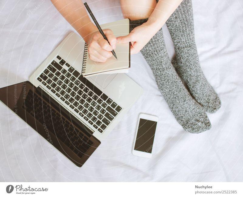 Frauenbeine in Socken und Schreiben auf dem Notebook über Laptop im Bett Lifestyle kaufen Stil Winter Schlafzimmer Arbeit & Erwerbstätigkeit Business Telefon