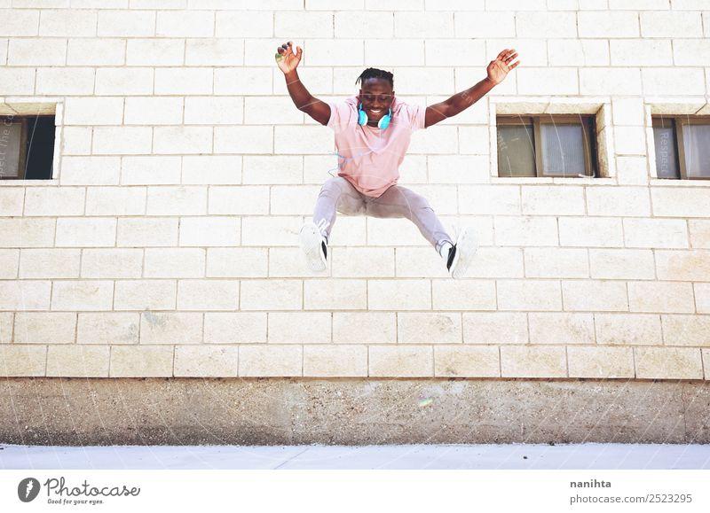 Glücklicher junger Mann, der an einem urbanen Ort springt. Lifestyle Stil Freude Gesundheit sportlich Wellness Leben Wohlgefühl Freizeit & Hobby Freiheit