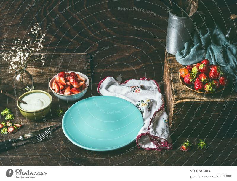 Leerer blauer Teller auf dunklem, rustikalem Holzküchentisch mit Erdbeeren und Joghurt in Schalen. Landhausstil mit Beeren im Hintergrund, Stilleben. Platz für Ihr Design, Ihre Rezepte, Ihren Text oder Ihre Produkte