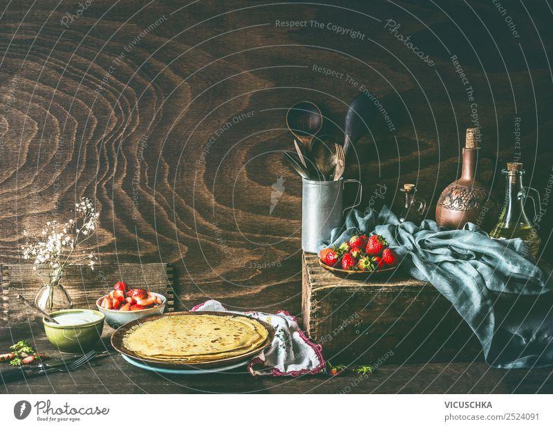 Ländliches Stilleben mit hausgemachten Crêpes auf dunklem, rustikalem Holzküchentisch mit Erdbeeren und Joghurt in Schalen . Land Stillleben selbstgemacht