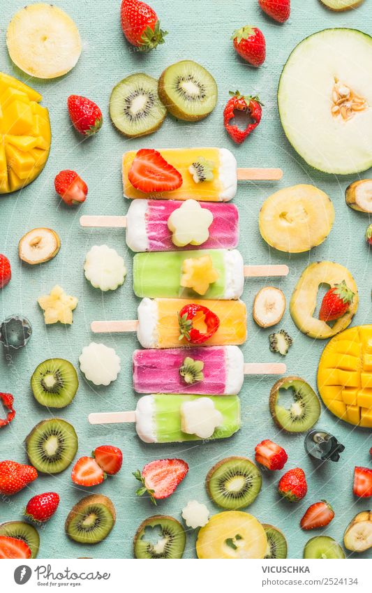 Colorful variety of Ice cream popsicles with fresh sliced fruits and berries ingredients on light blue background, top view, flat lay. Frozen tropical juices. Homemade ice cream lined up in a row