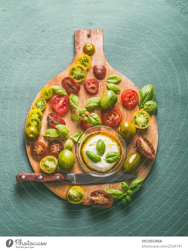 Bunte Tomaten mit Mozzarella und Messer auf Schneidebtrett Lebensmittel Käse Gemüse Ernährung Mittagessen Bioprodukte Vegetarische Ernährung Diät