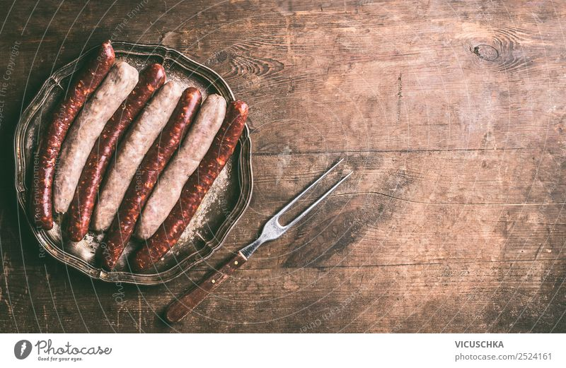 Bratwürste mit Fleischgabel Lebensmittel Wurstwaren Ernährung Geschirr Design Tisch Grill Stil Hintergrundbild Bratwurst Auswahl Gabel Holztisch Grillen