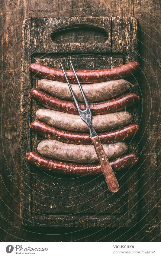 Bratwürste mit Fleisch Gabel Lebensmittel Wurstwaren Ernährung Stil Design Party Grill Bratwurst Auswahl Schneidebrett Holztisch Grillen Essen rustikal dunkel