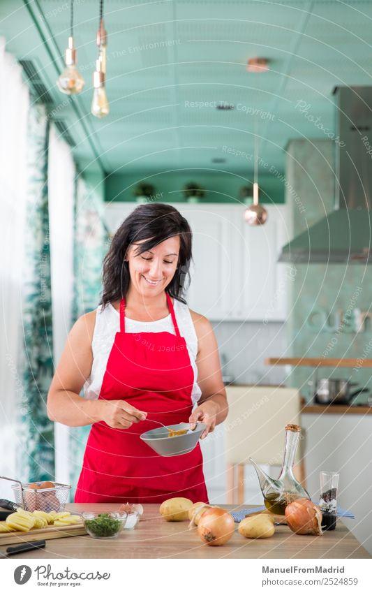 Köchin, die ein Rezept zubereitet. Ernährung Teller Glück Tisch Küche Mensch Frau Erwachsene Hand Holz Lächeln modern Küchenchef Koch vorbereitend Spanisch