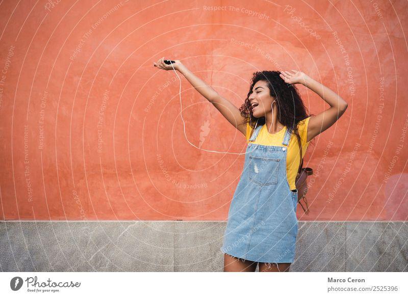schönes gemischtes Mädchen, das auf der Straße fröhlich der Musik lauscht Afrikanisch schwarz blau braune Haare lässig celular krause Haare niedlich Tanzen Tag