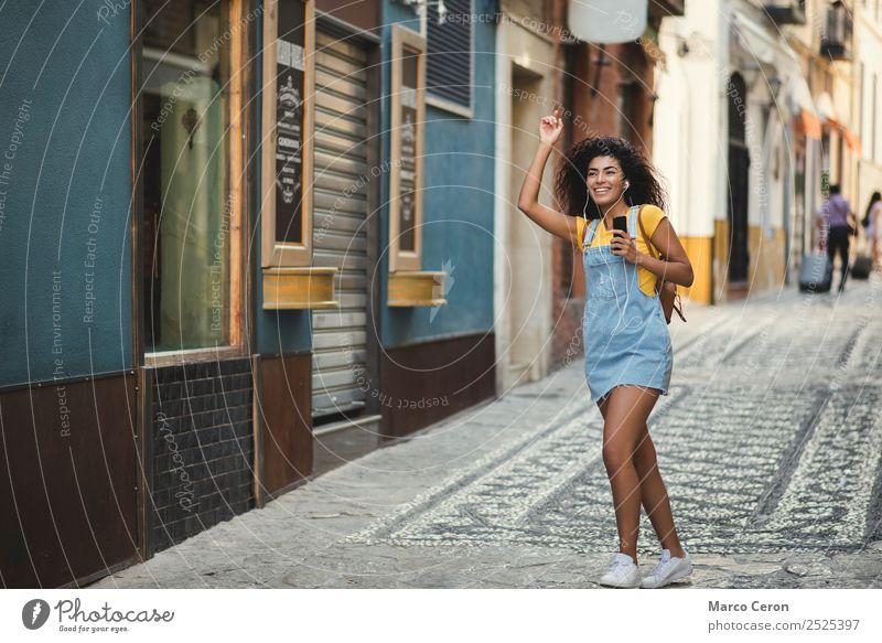 schönes gemischtes Mädchen, das der Musik lauscht und glücklich auf der Straße geht Afrikanisch Rucksack schwarz blau braune Haare lässig celular Farben