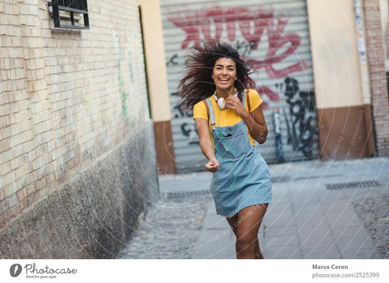 hübsches afrikanisches Mädchen, lässig gekleidet mit Kopfhörern, das fröhlich auf der Straße geht und Musik hört Afrikanisch Rucksack schön schwarz blau