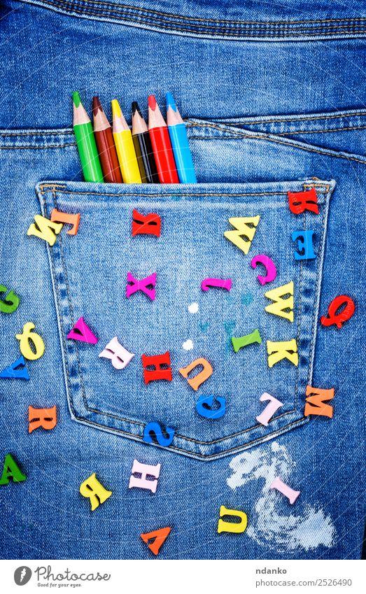 mehrfarbige Holzbuchstaben Design Schule Hose Jeanshose Stoff Schreibstift schreiben hell blau gelb rot weiß Farbe Kreativität Stil Alphabet Brief gestreut