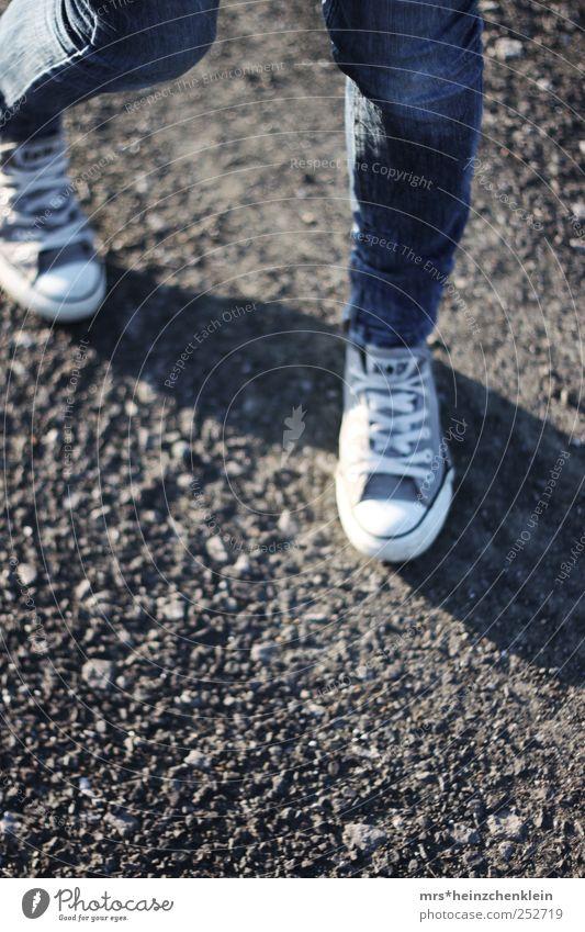 Spaziergang im Herbst Mensch Jugendliche blau weiß Bewegung Beine Mode braun Erde Schuhe laufen Jeanshose rennen drehen Chucks Eile