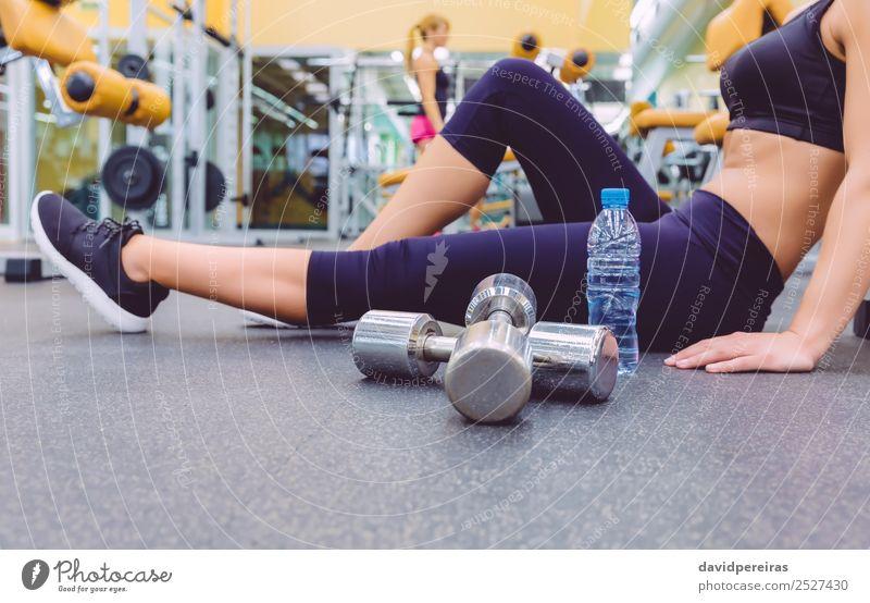 Frau, die sich ausruht und Freundin, die Kurzhantel-Übungen im Fitnessstudio macht. Flasche Lifestyle Glück schön Körper Freizeit & Hobby Club Disco Sport