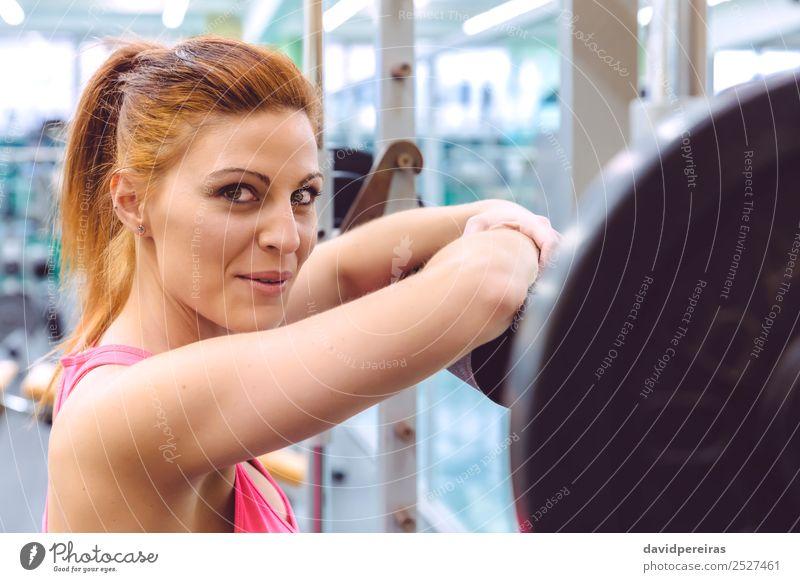 Frau lächelt und ruht sich nach dem Training über der Langhantel aus. Lifestyle Freude Glück schön Körper Sport Fotokamera Mensch Erwachsene Arme Fitness