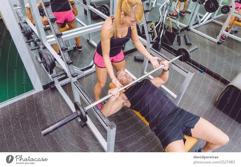 Frauentrainerin hilft dem Mann beim Bankdrücken-Training Sport Schule Erwachsene Freundschaft Fitness authentisch stark Mädchen Personal Trainerin Muskulatur