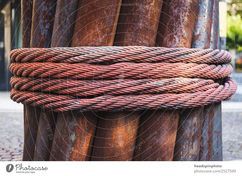 Eisenskulptur aus Eisrohren und Stahlseil Seil Industrie Kunst Industrieanlage Metall Rost drehen authentisch stark Verlässlichkeit Kraft Teamwork Verfall
