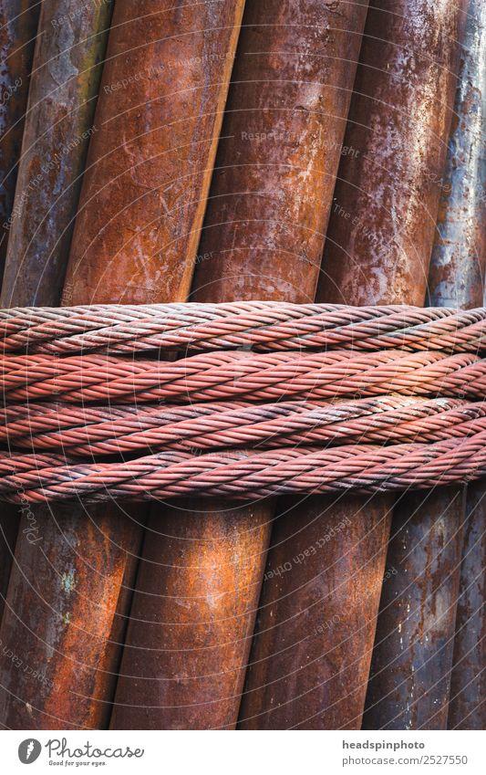 Mit Stahlseil umwickelte rostige Eisenrohre Kunst Metall Industrie Schnur Baustelle Seil Sicherheit festhalten Kabel Bauwerk Zusammenhalt Rost Stahlkabel
