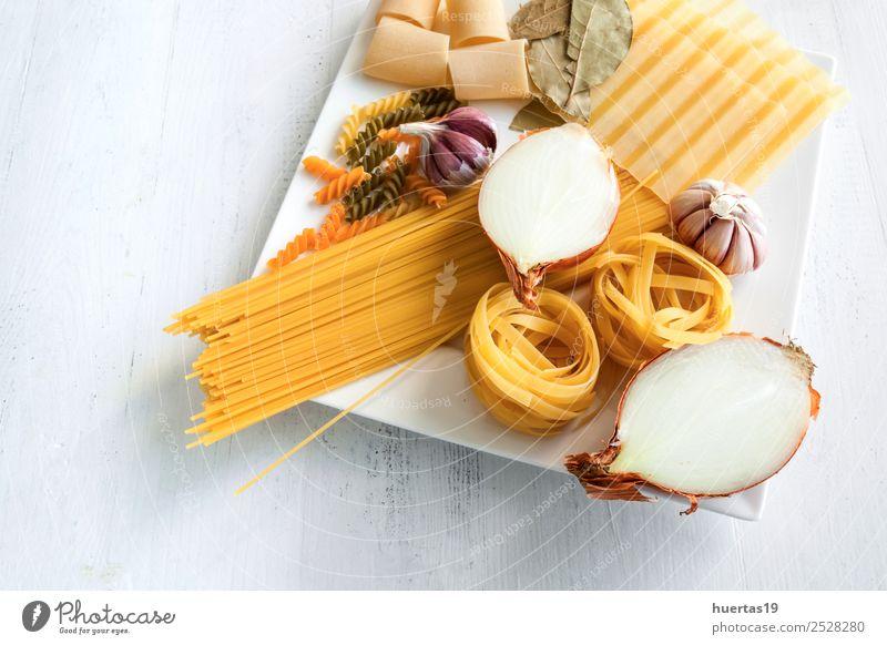 Italienische rohe Nudeln Lebensmittel Italienische Küche Geschirr Teller Gesunde Ernährung gelb grün Spätzle Zwiebeln Knoblauch Olivenöl Spaghetti Fettuccin