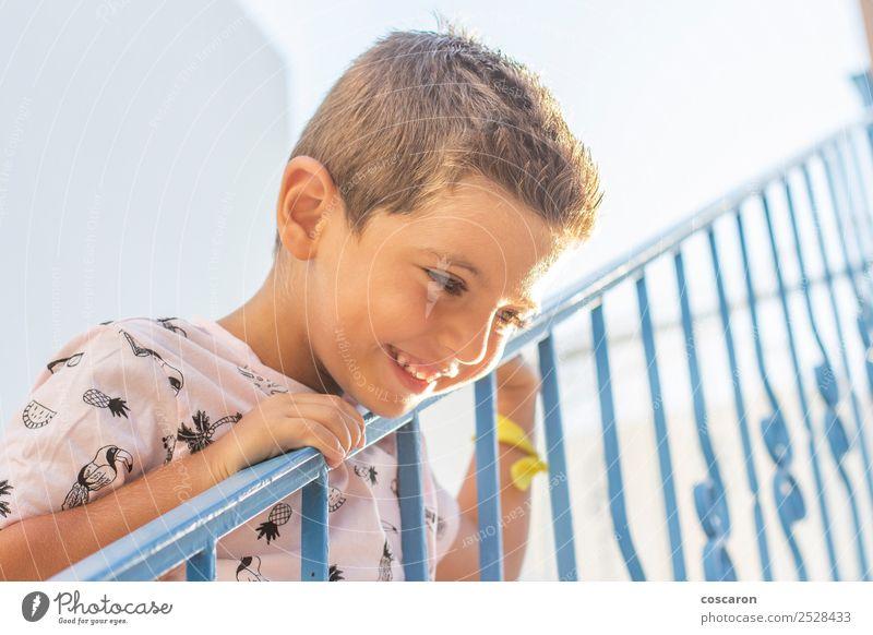 Kleiner Junge, der sich auf ein Geländer in einem weiß-blauen Dorf stützt. Lifestyle Freude Glück schön Gesicht Ferien & Urlaub & Reisen Tourismus Sommer