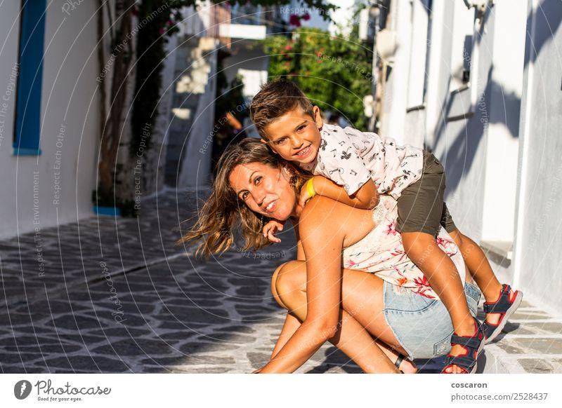 Junge klettert auf dem Rücken seiner Mutter auf der Straße eines griechischen Dorfes Lifestyle Freude Glück schön Spielen Ferien & Urlaub & Reisen Tourismus