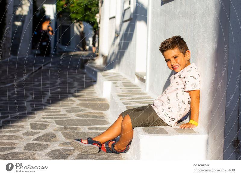 Kleiner Junge, der auf einer Steinbank saß. Ferien & Urlaub & Reisen Tourismus Sommer Insel Haus Landschaft Blume Dorf Stadt Gebäude Architektur Straße Lächeln