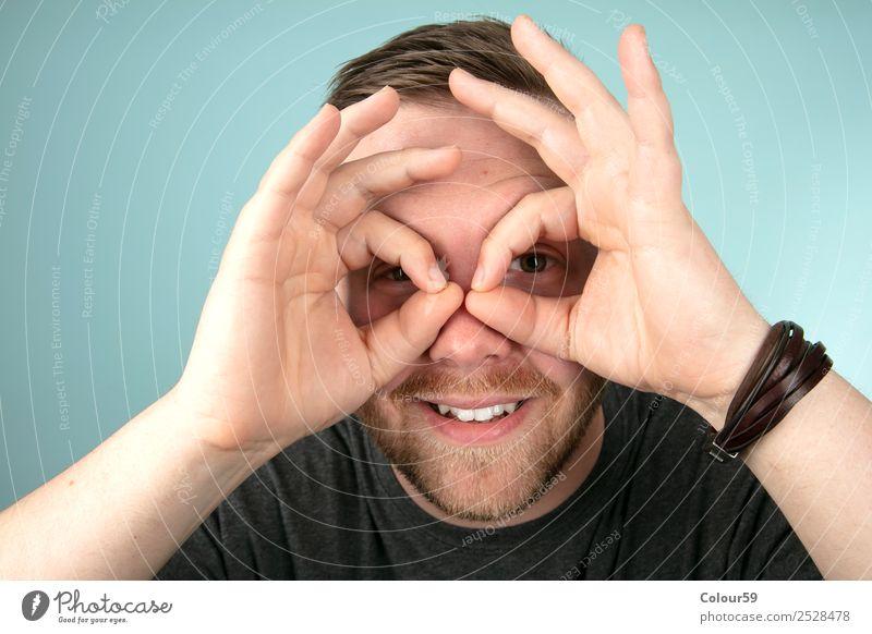 Junger Mann macht mit seinen Fingern eine Geste um seine Augen Stil Mensch maskulin Jugendliche Kopf Freundlichkeit Fröhlichkeit communication eyeglasses eyes
