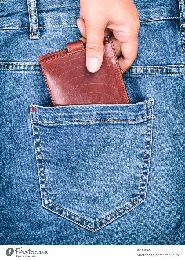 weibliche Hand klammert sich an eine Handtasche. Stil Geld Business Mensch Frau Erwachsene Mode Bekleidung Hose Jeanshose Stoff Leder festhalten blau braun