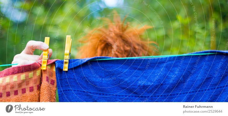 eine Frau hängt draußen Wäsche auf eine Wäscheleine feminin Erwachsene Haare & Frisuren Hand 1 Mensch rothaarig Arbeit & Erwerbstätigkeit Sauberkeit Tatkraft
