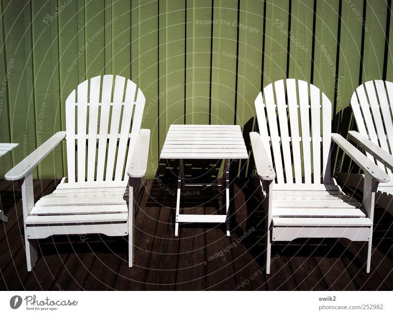 Strenges Design Stuhl Tisch Holz eckig einfach hell braun grün weiß hart Holzwand Linie parallel Geometrie Linearität streng Farbfoto Gedeckte Farben