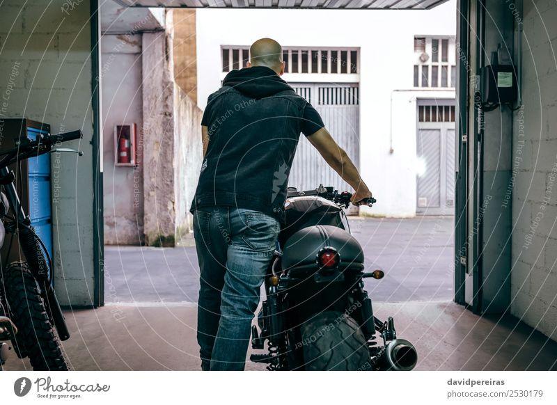 Mann mit Custom-Motorrad, der die Garage verlässt. Lifestyle Stil Ferien & Urlaub & Reisen Ausflug Mensch Erwachsene Straße Jeanshose Glatze stehen tragen