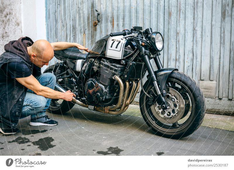 Biker-Check mit einem Motorrad Lifestyle Stil Ausflug Mensch Mann Erwachsene Straße Fahrzeug Turnschuh Glatze authentisch retro schwarz Motorradfahren geduckt