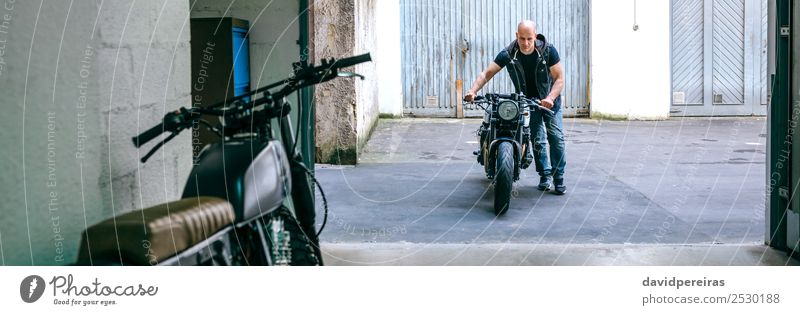 Biker mit dem Motorrad in die Werkstatt Lifestyle Stil Ferien & Urlaub & Reisen Ausflug Mensch Mann Erwachsene Straße Fahrzeug Glatze stehen tragen authentisch